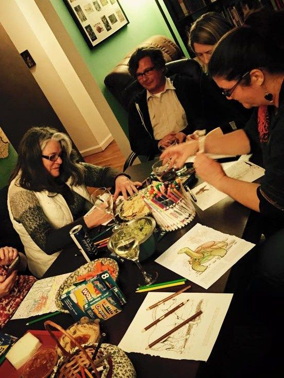 A group of adult friends at a coloring book party