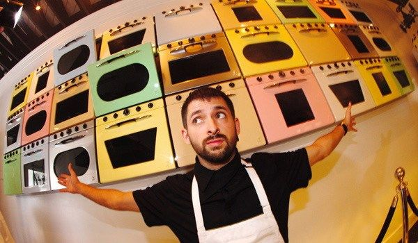 Johnny Cupcakes founder John Earle in front of his Los Angeles' shop's wall of ovens.