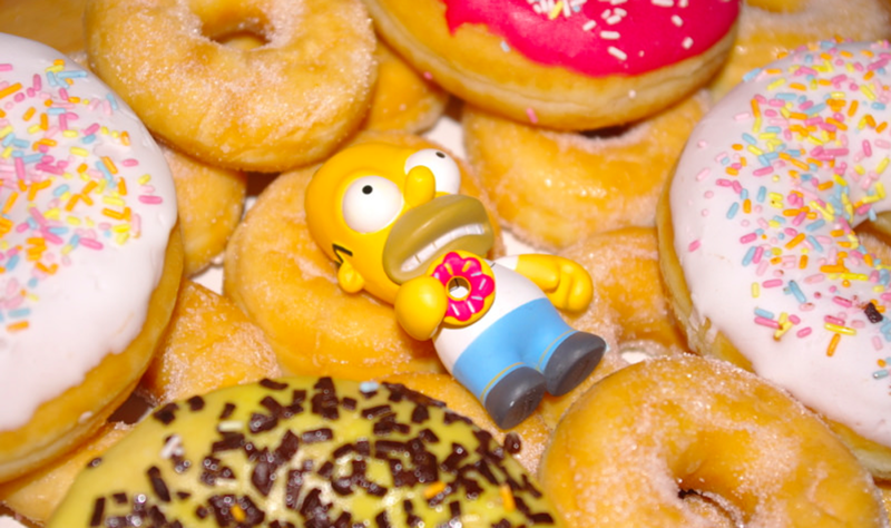 Homer Simpson toy sitting on donuts